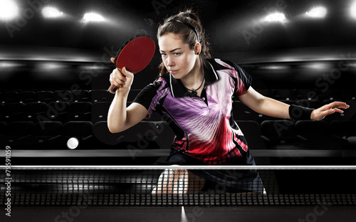 Young pretty sporty girl playing table tennis on black