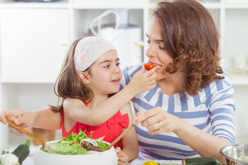 Mother and daughter tasting food they are preparing