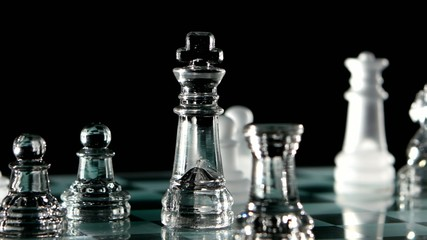 Glass chess game on a black background.