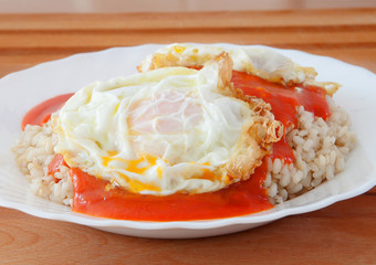 Fried egg with rice overcooked and tomato