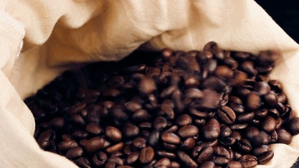 a lot of coffee beans falling down in a canvas sack