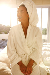 beautiful young girl in a bathrobe wipes her hair with a towel