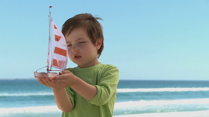 MS OF A BOY PLAYING WITH A TOY BOAT
