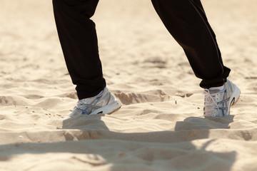 Jogging walking. Female legs hiking on the beach.