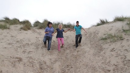 Teenagers running down the dunes