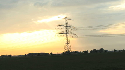 Zoom out on electricityy pylon and cables at sunset