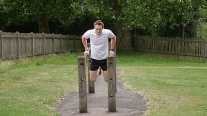 Male fitness training on parallel dip bar
