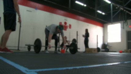 Various shots of people working out in a cross-fit type gym.