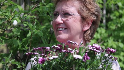 Portrait of mature female with flowers in garden centre