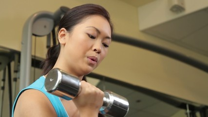 Woman exercising with dumbbells and drinking water