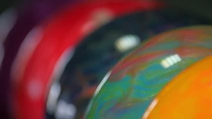 Hand taking multicolored ball from bowling ballmachine. Сamera