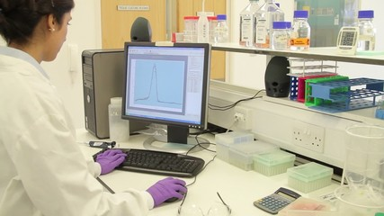 Scientist looking at graphs (dissociation curves from an RT-PCR) on computer screen in lab