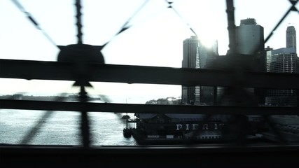 WS POV Car crossing East River with view of Manhattan Financial District and Brooklyn Bridge / New York, New York, USA