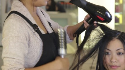 MS, Hairdresser drying and brushing hair of female in hair salon