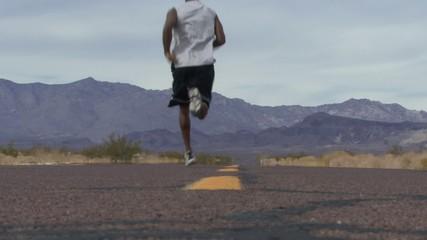 Male running along road in the desert