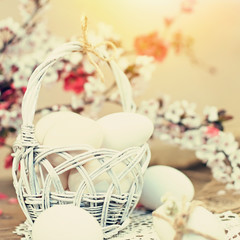 Easter eggs in white basket with pink and white spring flowers