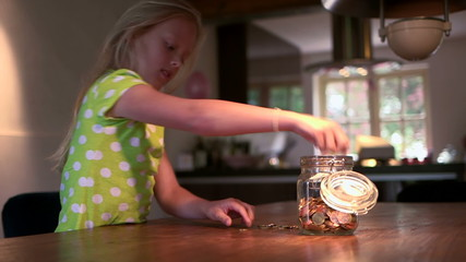 Girl filling coins jar