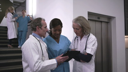 Doctors and nurse using digital tablet