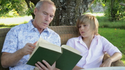 MS, Father and son sitting on bench in garden reading and talking