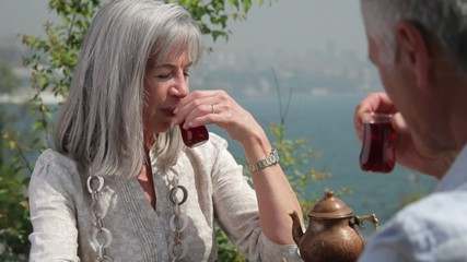 Couple drinking tea on terrace looking out over river Bosphorus Turkey Istanbul
