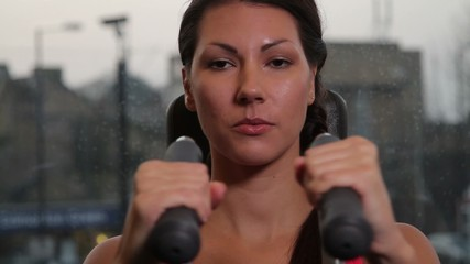 Female working out in gym on exercise machine