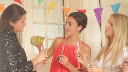 Female opening bottle of wine with friends at party