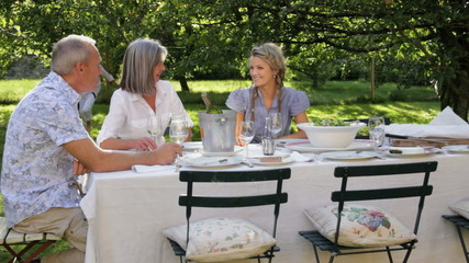 WS, Family in garden together around table for dinner