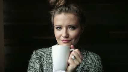 Young smiling woman looking at camera holding cup of tea.