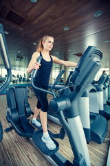 beautiful girl doing indoor biking in a fitness club