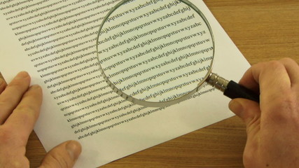 Looking trough Magnifying Glass at small print in contract
