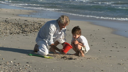 LS OF A GRANDFATHER AND GRANDSON MAKING A SANDCASTLE
