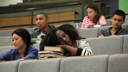 Female student falling asleep on books in lecture theatre, during class