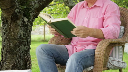 Male in garden reading book