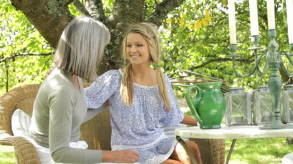Mother and daughter in garden greeting and talking