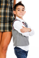 Little boy posing near mother legs.