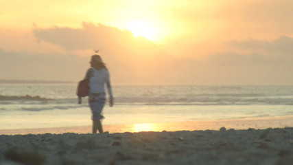 LS OF A YOUNG WOMAN WALKING ALONG A BEACH