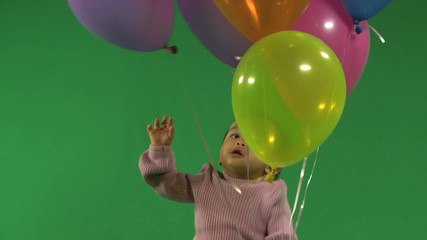 MS OF A BABY RELEASING BALLOONS