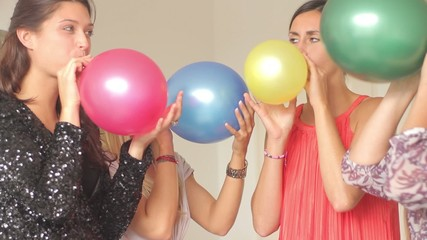 Females friends blowing up balloons at party