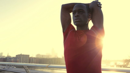 Male stretching in red top, City of London, Olympic city in the background, UK