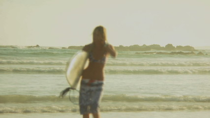 LS OF A YOUNG WOMAN WALKING FROM THE SEA CARRYING A SURFBOARD