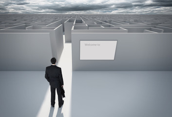 Businessman standing in front of entrance to maze.
