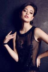 elegant woman with dark hair in luxurious black dress