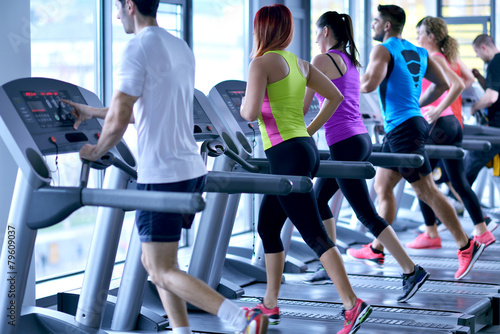 Group of people running on treadmills - 79609037