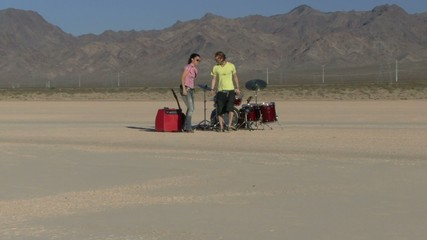 Male and female playing music in desert and walking away