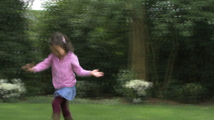 LS PAN OF A GIRL RUNNING THROUGH A SPRINKLER