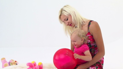 Mother And Her Baby Playing With Pink Balloon