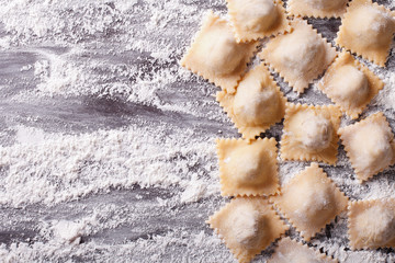 raw ravioli with flour on the table. horizontal top view