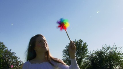 Female blowing on a pinwheel