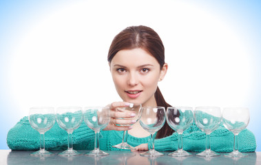 Woman watching seven empty glasses