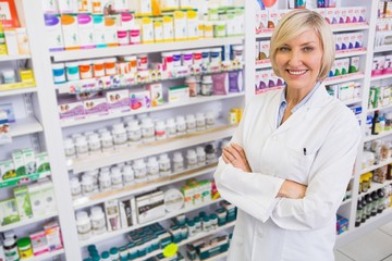 Blonde pharmacist with arms crossed smiling at camera